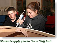 Students apply glue to Bevin skiff hull