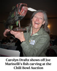 Carolyn Draftz shows off Joe Marinelli's fish carving at the Cili Bowl Auction