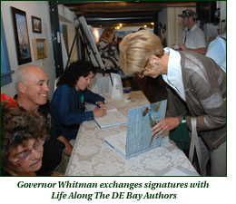 Governor Whitman exchanges signatures with Live Along The DE Bay authors