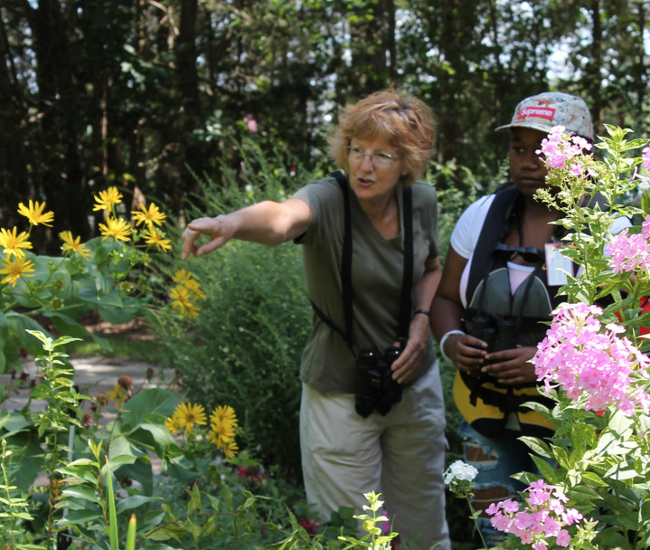 Christine points our flora and fauna in a wildflower garden