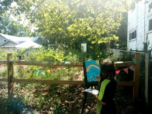 Child painting at Neighborhood Wildlife Garden Play Streets